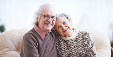 Image of a smiling, Elderly couple holding each other in their living room